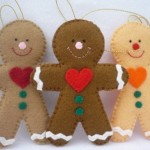 3 Sewn Felt Gingerbread men Christmas ornaments with red hearts and 2 green buttons on their fronts with ric rac white ribbon on hands and feet